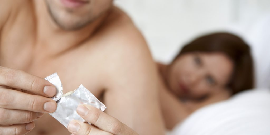 Man Opening Condom With Woman In Bed