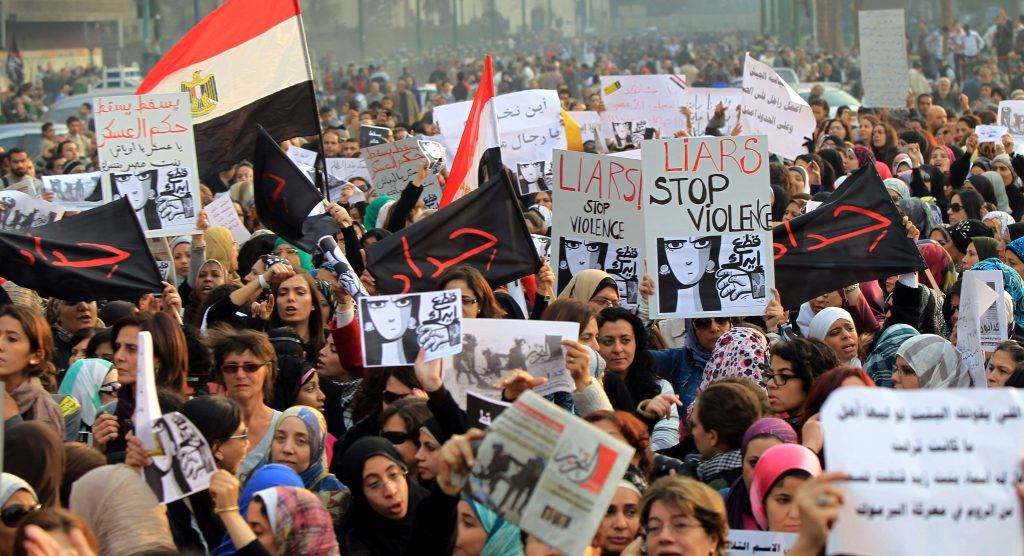 Egyptians hold signs during a protest in downtown Cairo to denounce the military's attacks on women and to call for an immediate end to the violence against protesters on December 20, 2011. AFP PHOTO/KHALED DESOUKI